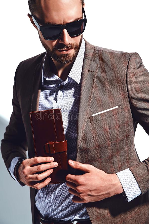 Handsome fashion stylish businessman model dressed in elegant suit. Portrait of handsome fashion stylish hipster businessman model dressed in elegant brown suit stock photography