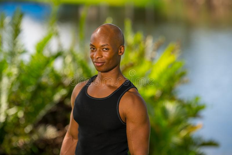 Portrait of a handsome fitness model posing in a park setting royalty free stock images