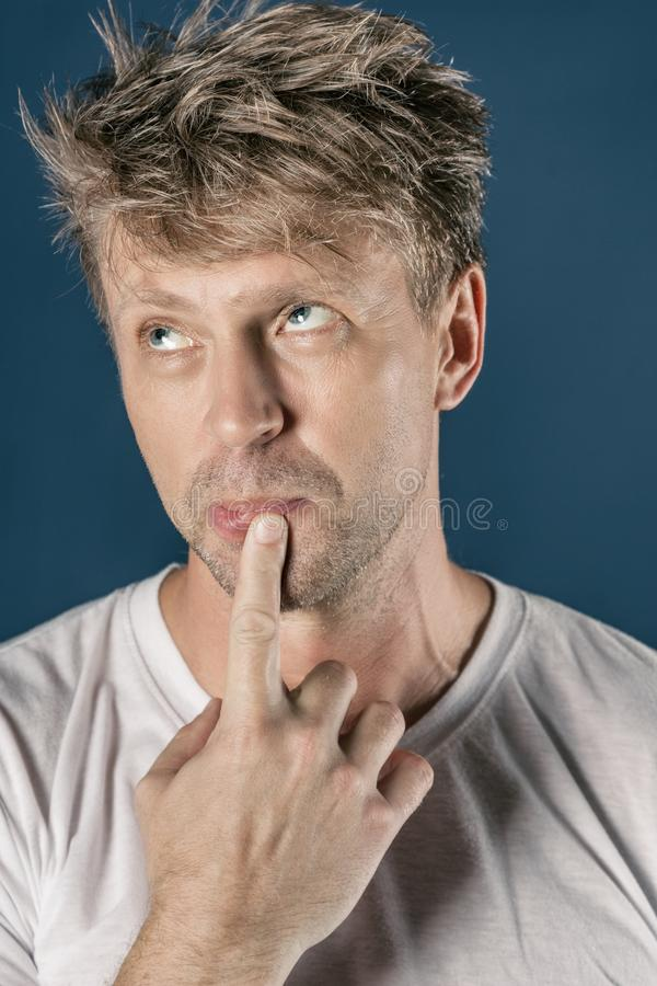 Portrait of handsome funny thoughtful man isolated over blue background stock photography