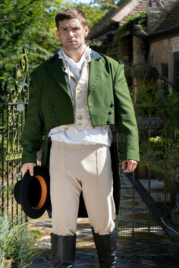 Portrait of handsome gentleman dressed in vintage costume, holding top hat in stately home courtyard. Portrait of attractive gentleman dressed in vintage costume stock image