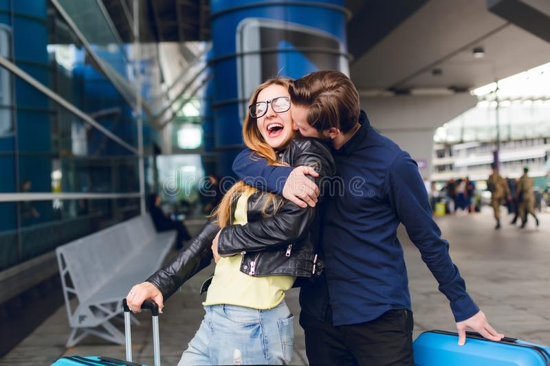 Portrait of handsome guy with beard in black shirt kissing girl with long hair outside in airport. She wears glasses.  stock image