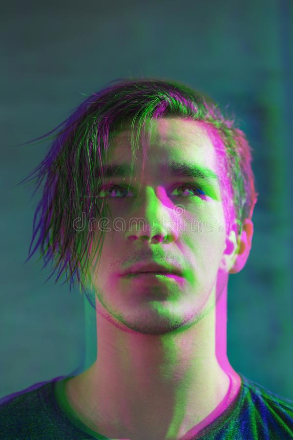 Portrait of a handsome guy with disheveled hair against a gray concrete wall. Digital signal glitch effect rgb shift, slices. S stock photos