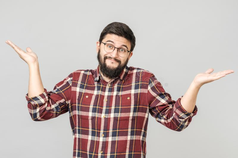Portrait of handsome guy looking upside and shrugging his shoulders. Showing there`s nothing he can do with situation. Facial expressions stock photography