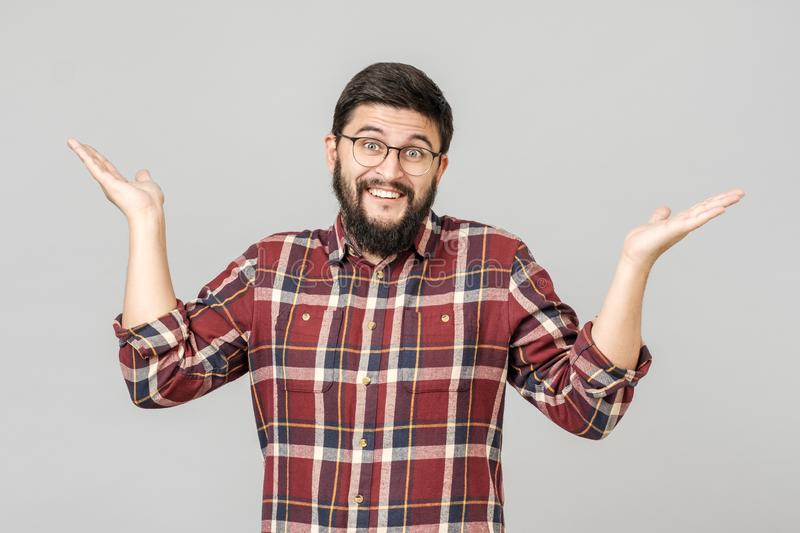 Portrait of handsome guy looking upside and shrugging his shoulders royalty free stock images