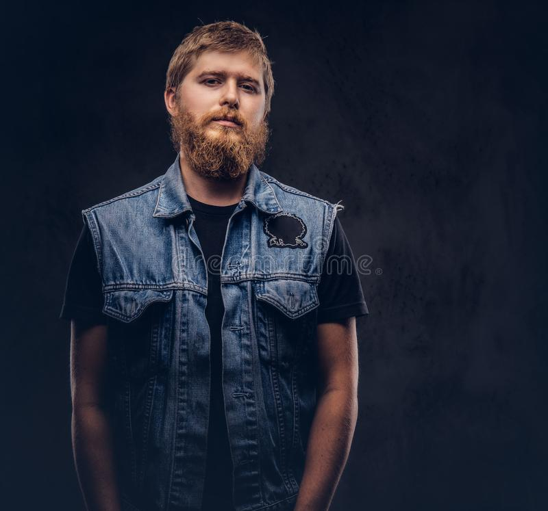 Portrait of a handsome hipster guy dressed in jeans jacket looking at a camera on a dark background. stock photography