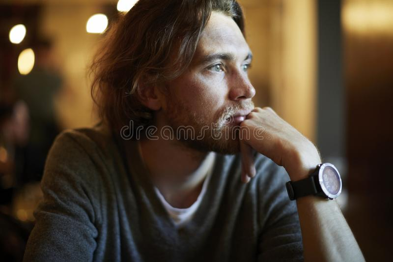 Portrait of handsome hipster guy with long hair and beard sitting in sunny cafe, resting near window. Romantic man looks lonely. stock images