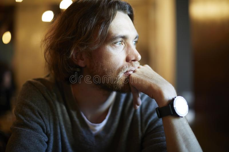 Portrait of handsome hipster guy with long hair and beard sitting in sunny cafe, resting near window. Romantic man looks lonely. royalty free stock photography