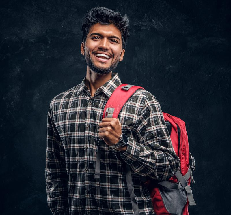 Portrait of a handsome Indian student with a backpack wearing a plaid shirt, smiling and looking at a camera. Studio photo against a dark textured wall royalty free stock images