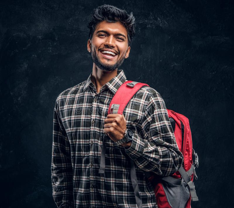 Portrait of a handsome Indian student with a backpack wearing a plaid shirt, smiling and looking at a camera. Studio photo against a dark textured wall stock images