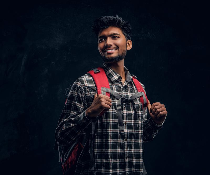Portrait of a handsome Indian student with a backpack wearing a plaid shirt, smiling and looking sideways. Studio photo against a dark textured wall stock photography