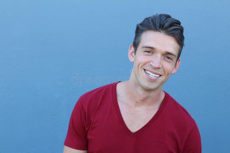 Portrait of a handsome latin man smiling, isolated over a blue background stock image