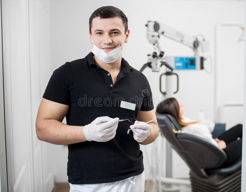 Portrait of handsome male dentist holding dental tools - probe and mirror at dental office. Dentistry. Portrait of handsome male dentist holding dental tools royalty free stock image