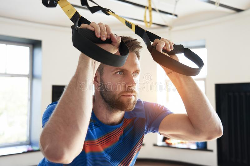 Portrait of handsome man athlete doing exercise alone with fitness belts in modern gym club, workout single sport, sun shining royalty free stock images