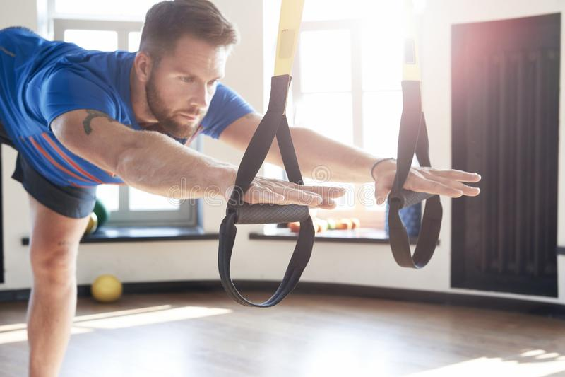 Portrait of handsome man athlete doing exercise alone with fitness belts in modern gym club, workout single sport, sun shining stock photos