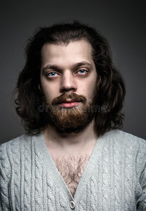 Portrait of a handsome man with a beard, long hair and big blue eyes royalty free stock image