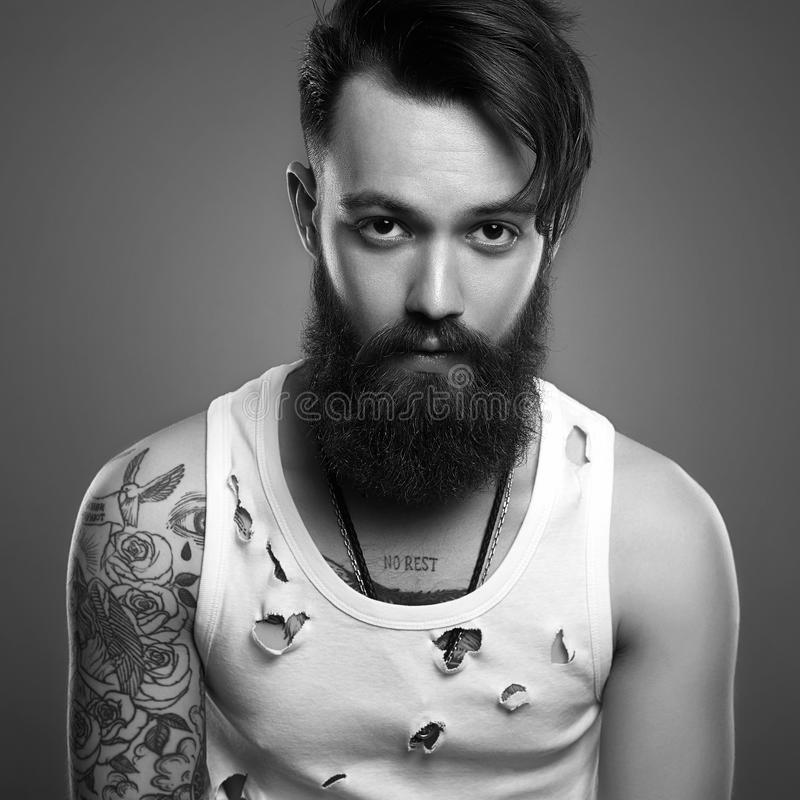 Portrait of handsome man with beard and tattoo. Black and white portrait of handsome man with beard and tattoo. bearded hipster boy in vintage torn dirty shirt royalty free stock image