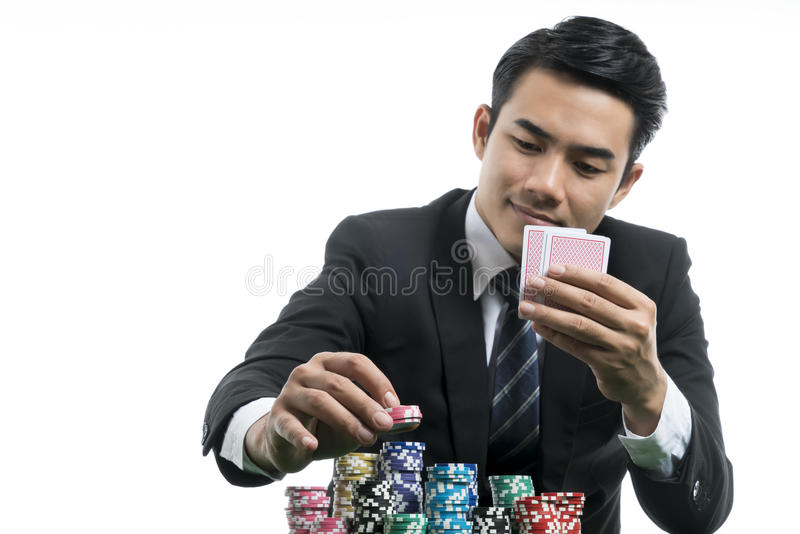 Portrait handsome man in black suit is putting piles of chips an royalty free stock photography