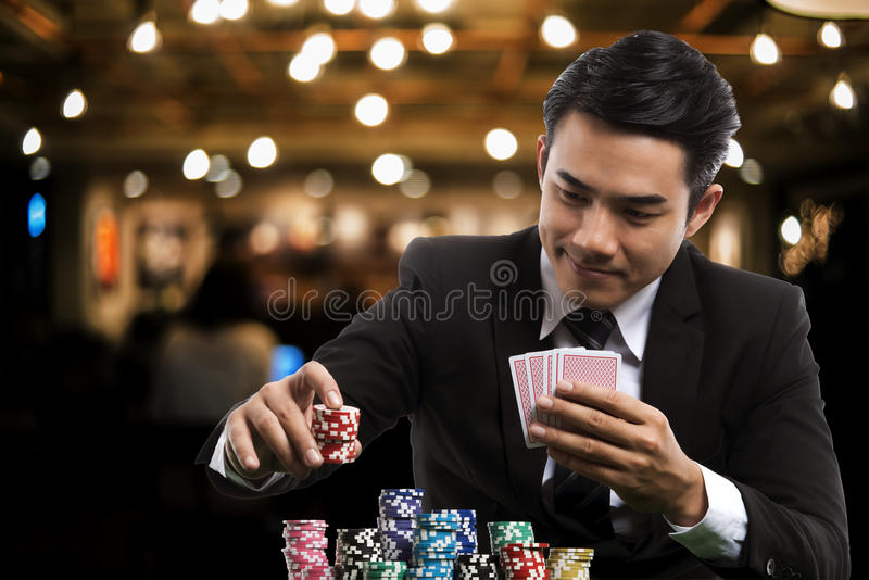 Portrait handsome man in black suit is putting stack of chips an royalty free stock photography
