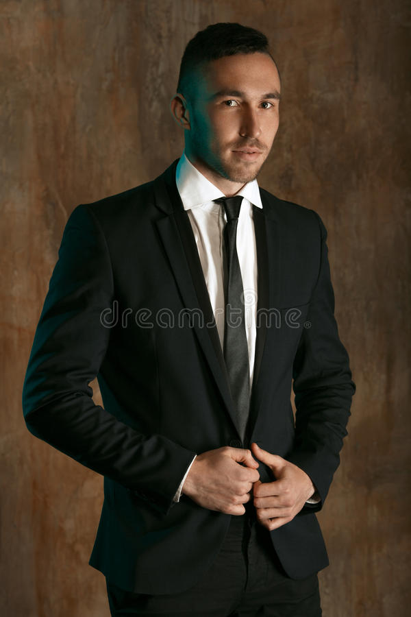 Portrait of a handsome man in a black suit who is posing over wall background royalty free stock image
