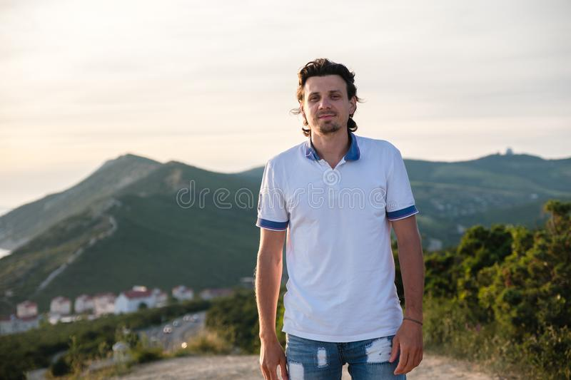 Portrait of a handsome man brunette in a light t-shirt on a background of mountains. Front view. stock photography