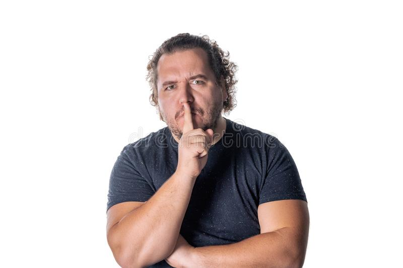 Portrait of handsome man cowering his mouth with his finger stock images