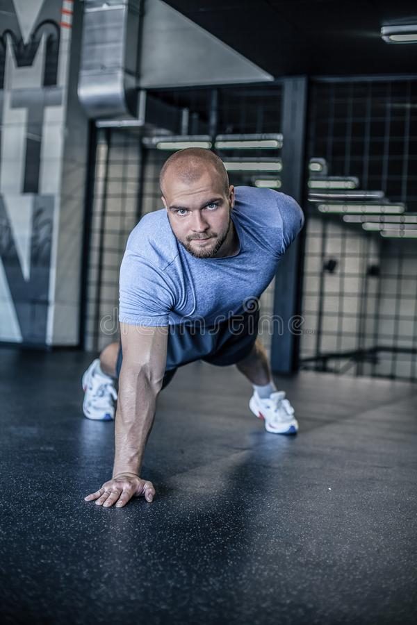 Portrait of a handsome man doing push ups exercise with one hand in fitness gym. dressed in a sports uniform. Portrait of a handsome man doing push ups exercise stock photo