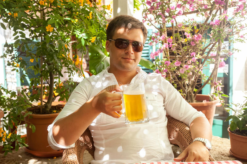 Portrait of handsome man drinking beer at restaurant at hot day royalty free stock photos