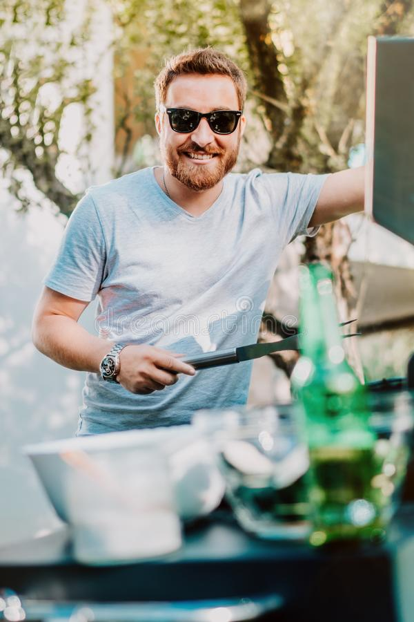 Portrait of handsome man enjoying barbecue party, cooking grill meat royalty free stock photos