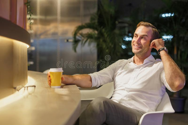 Portrait of a handsome man in the interior with coffee and earphones stock photo