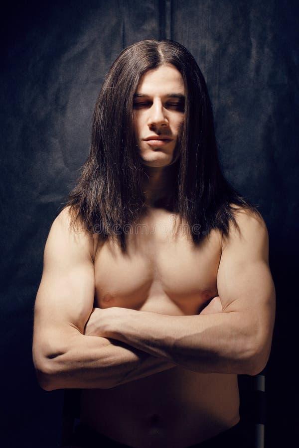 man with long dark hair naked
