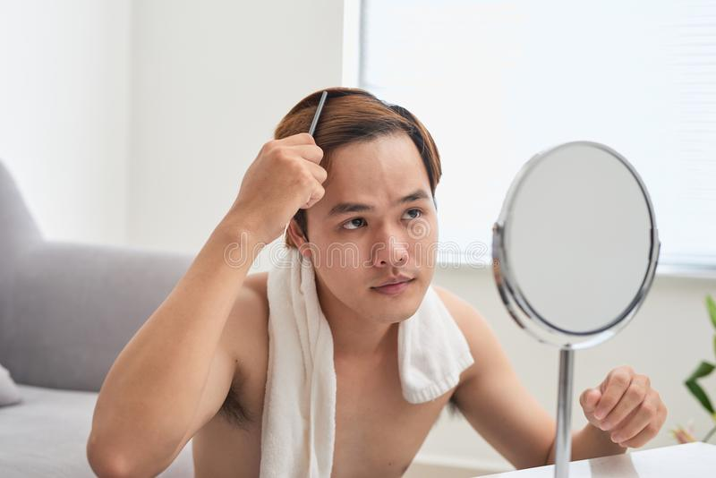 Portrait of handsome man looking at himself in mirror and brushing his hair. stock photos