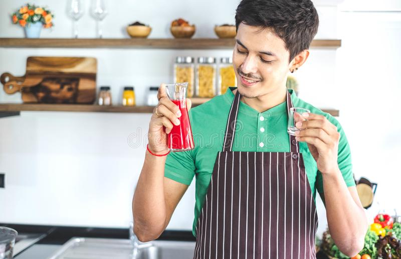 A portrait of handsome man making cold presses fruit juice in a modern kitchen. royalty free stock photography