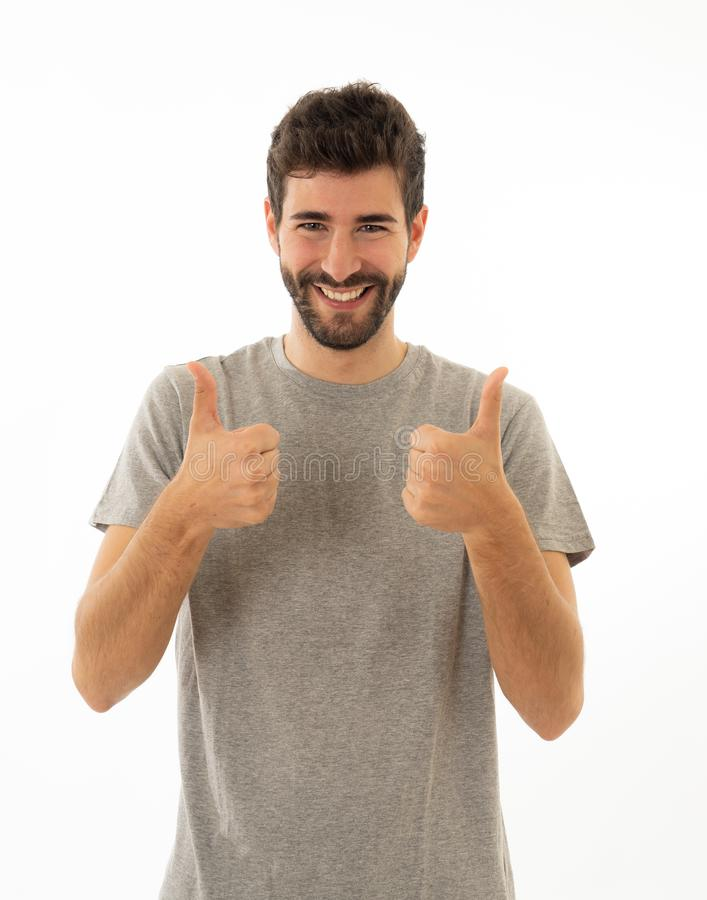 Portrait of handsome man making thumbs up gestures feeling happy and successful royalty free stock photo