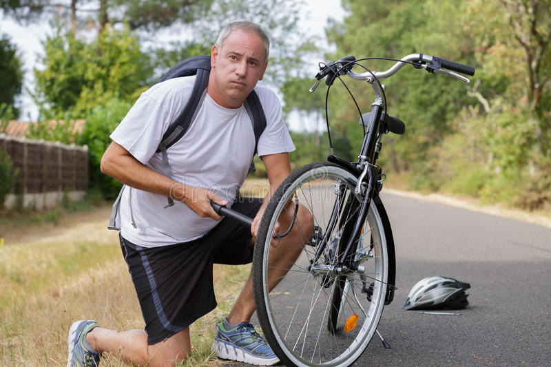 Portrait handsome man pumping bicycle tires at park stock photography
