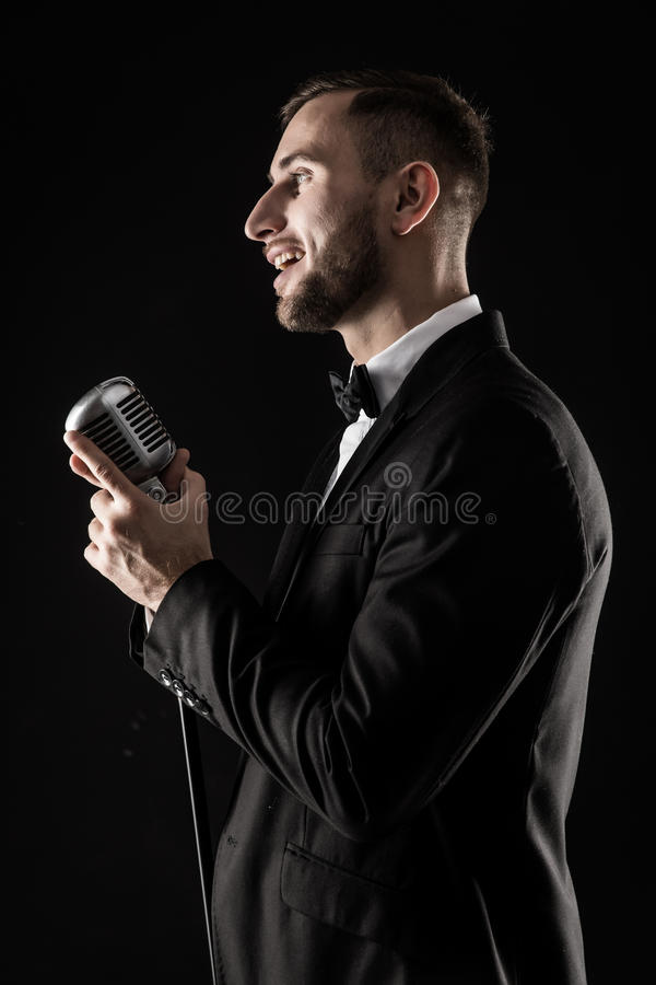 Portrait of handsome man sing on microphone on black background. stock images