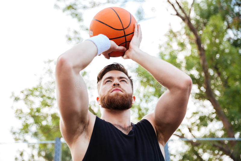 Portrait of a handsome man in sports wear playing basketball stock photography