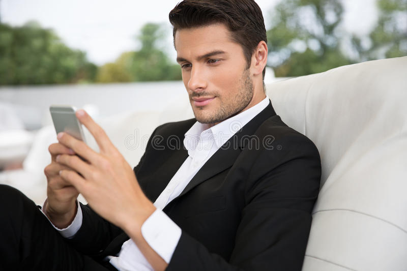 Portrait of a handsome man using smartphone. Outdoors in restaurant royalty free stock images