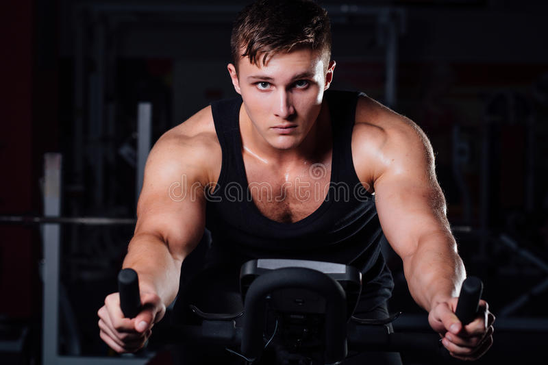 Portrait of a handsome man workout on fitness the exercise bike dark at gym. stock photos