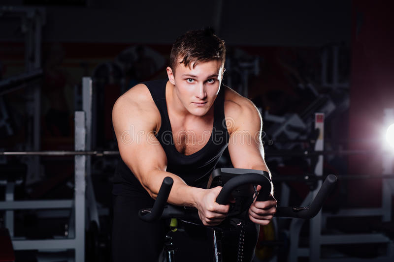 Portrait of a handsome man workout on fitness the exercise bike dark at gym. stock image