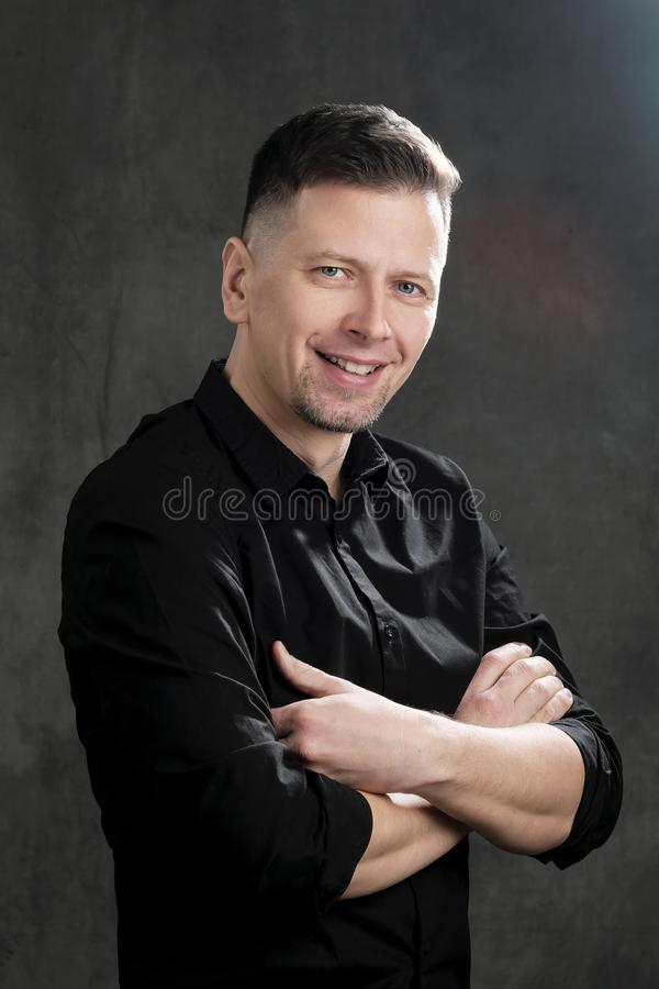 Portrait of a handsome man 40 years old on a dark artistic background close-up. Brunette, with gray hair, black beard royalty free stock photos