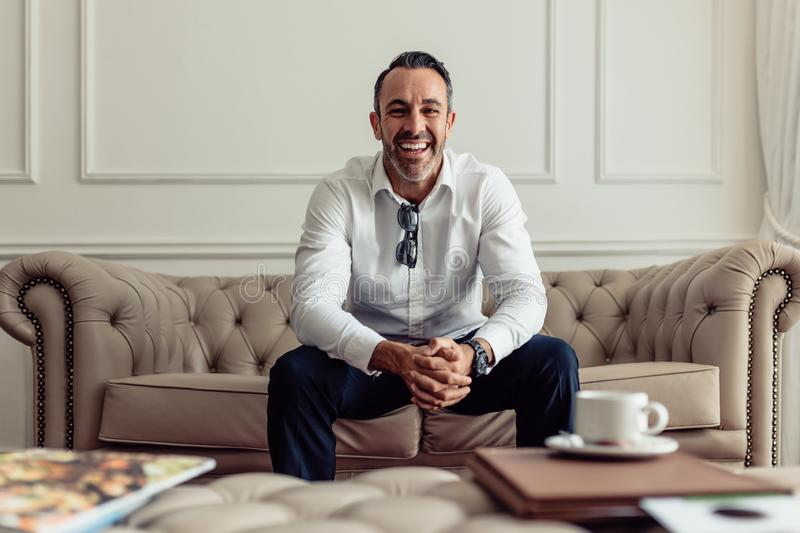 Portrait of handsome mature businessman sitting on sofa in hotel room. Cheerful CEO staying in luxurious hotel room on business royalty free stock photos