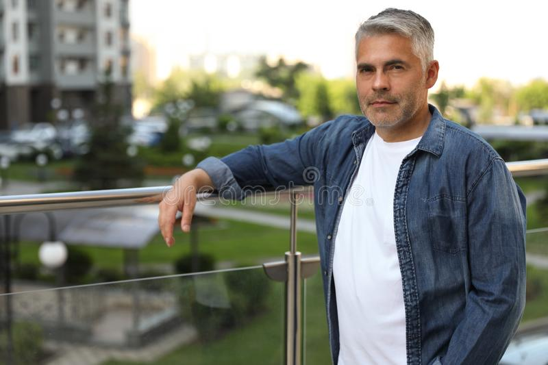 Portrait of handsome mature man in city stock photos