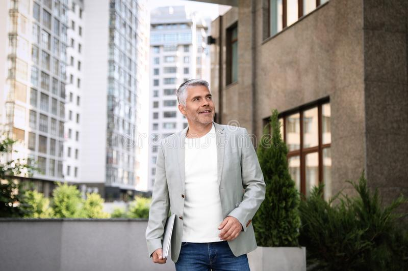 Portrait of handsome mature man with laptop in city royalty free stock photography