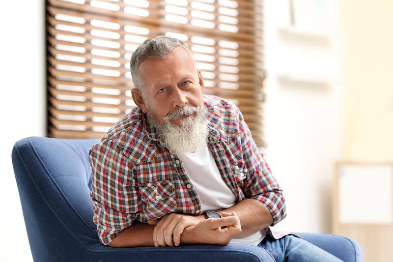 Portrait of handsome mature man sitting in armchair royalty free stock photo