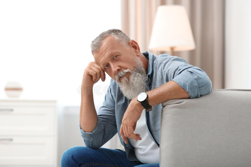 Portrait of handsome mature man sitting on sofa stock photography