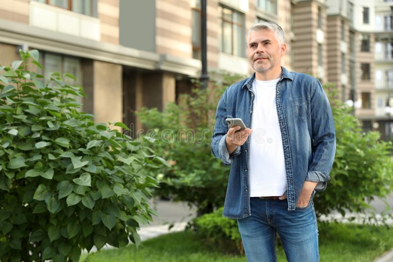 Portrait of handsome mature man using mobile phone in city stock images