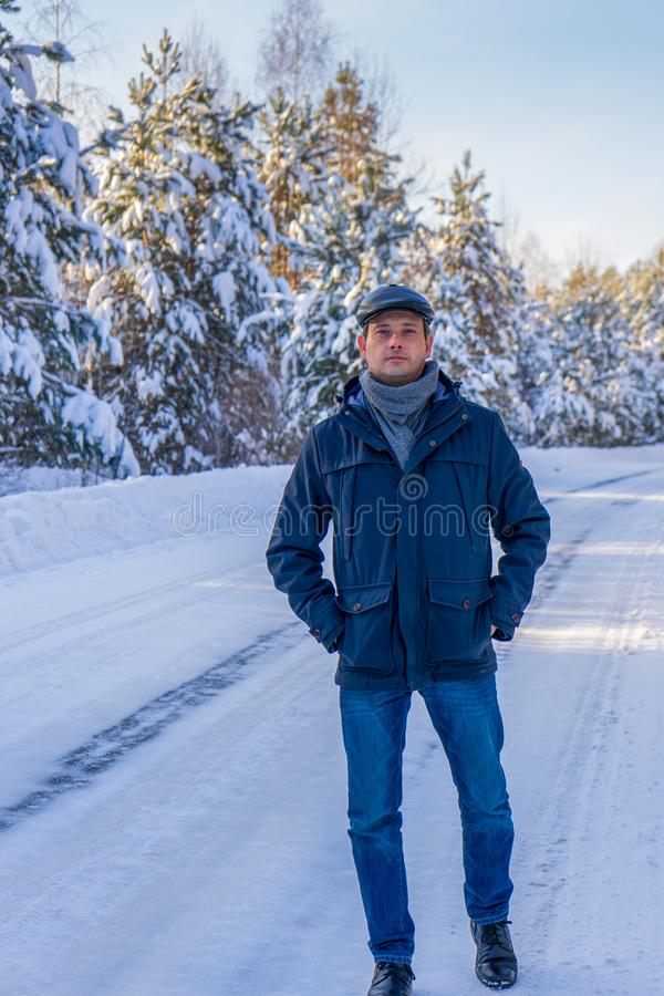 Portrait of handsome middle-aged man against beautiful winter snowy landscape. Man walking along forest road in sunny frosty day. royalty free stock images