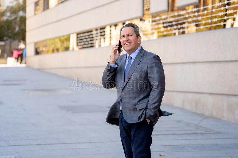 Portrait of handsome middle aged smart businessman walking in the city talking on mobile phone stock images