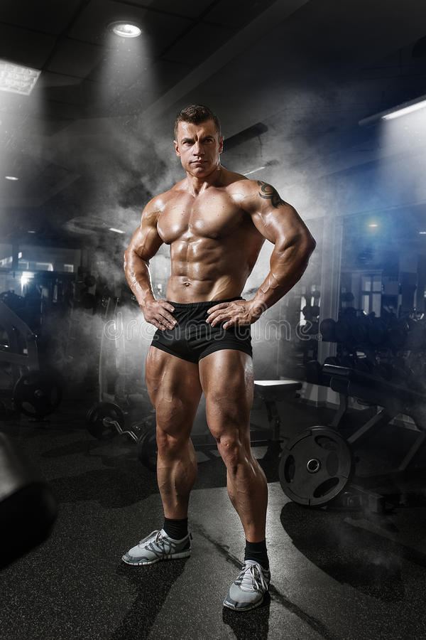Portrait of a handsome muscular bodybuilder posing in gym stock photography