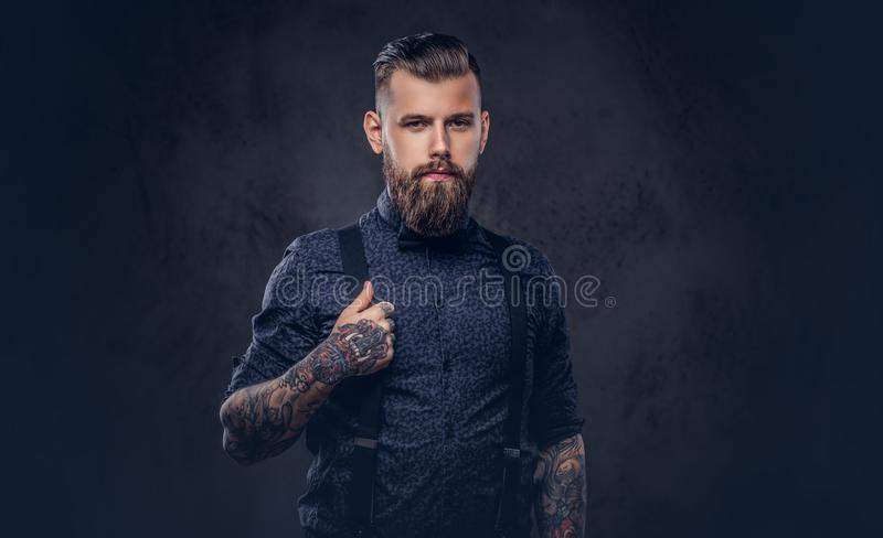 Portrait of a handsome old-fashioned hipster in a blue shirt and suspenders, posing in a studio. stock image